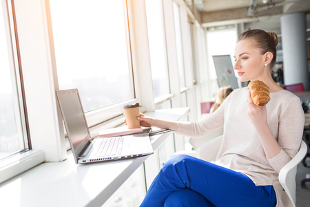 A picture of woman having lunch at work. She is eating a croissant and have a cup of coffee on the table. Also girl is watching something on the laptop.