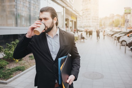 Busy man is in a hurry, he does not have time, he is going to talk on the phone on the go. Businessman doing multiple tasks on the hood of the car. Multitasking business person is drinking cofee
