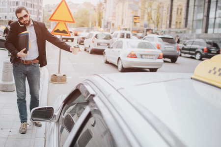 Bearded businessman with coffee cup catching a taxi. He does not have time, he is going to talk on the phone on the go. Man doing multiple tasks. Multitasking business male persone. Reklamní fotografie - 100154339