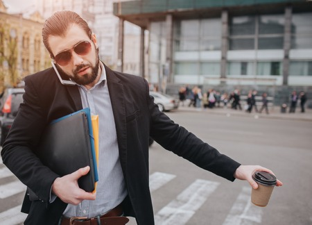 Bearded businessman with coffee cup catching a taxi. He does not have time, he is going to talk on the phone on the go. Man doing multiple tasks. Multitasking business male persone.