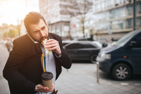 Busy man is in a hurry, he does not have time, he is going to eat snack on the go. Worker eating, drinking coffee, talking on the phone, at the same time. Businessman doing multiple tasks. Multitasking business person. Reklamní fotografie