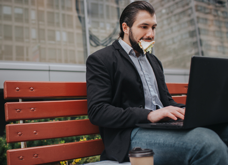 Busy man is in a hurry, he does not have time, he is going to eat snack outdoors. Worker eating and working with documents on the laptop at the same time. Businessman doing multiple tasks. Multitasking business person.