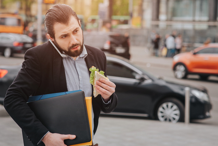 Busy man is in a hurry, he does not have time, he is going to eat snack on the go. Worker eating, drinking coffee, talking on the phone, at the same time. Businessman doing multiple tasks. Multitasking business person. 스톡 콘텐츠