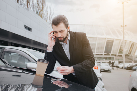 Busy man is in a hurry, he does not have time, he is going to talk on the phone on the go. Businessman doing multiple tasks Sale of cars, the buyer or seller is the filling of blank forms on the car. Reklamní fotografie