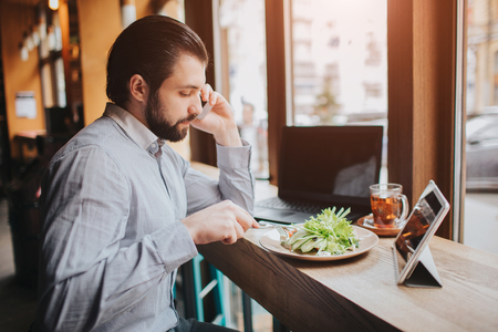 Busy man is in a hurry, he does not have time, he is going to eating and working. Worker eating, drinking coffee, talking on the phone, at the same time. Businessman doing multiple tasks. Multitasking business person. Reklamní fotografie