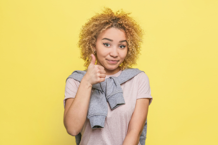 Satisfied and beloved girl is showing her big thumb up to the camera. She is satisfied. Isolated on yellow background