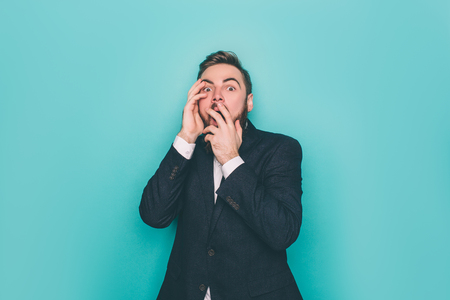 Horizontal picture of young man. He is scared and terrified. Guy has closed the part of his face with his hands. Isolated on blue background