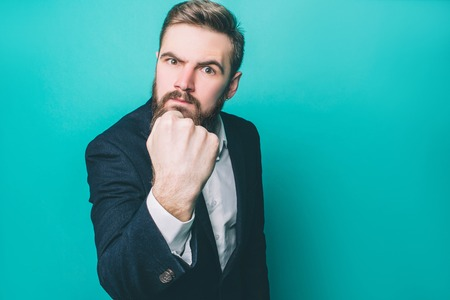 Serious and brutal guy is showing his fist to camera. Man is angry. He is not hiding his emotions. Isolated on blue background