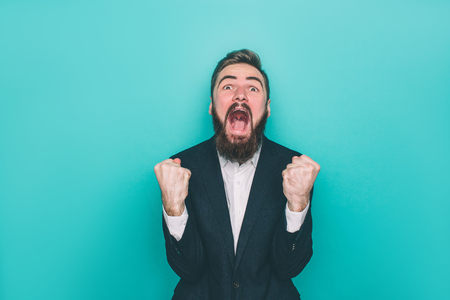 Man is screaming and yelling. He is absolutely happy. Guy is looking to camera and holding his fingers in fist. Isolated on blue background 版權商用圖片