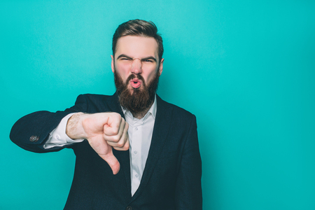 Guy is standing and showing his big thumb down. He is not happy and satisfied. This man is upset. Isolated on blue background