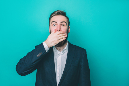 Bearded guy is closing his mouth with the hand. He looks scared and terrified. Isolated on blue background