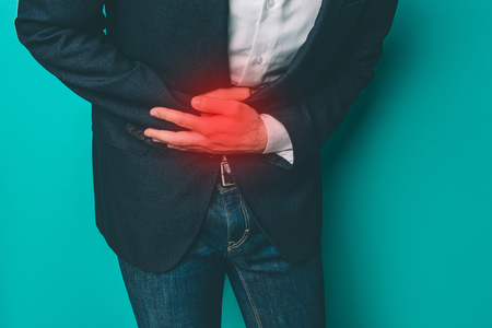 A picture of man that has a pain in stomach. He is holding both hands on the place where the pain is. That place is marked with red point. Isolated on blue background