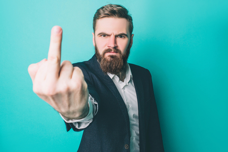 Brutal man is showing the middle finger to the camera. He is very serious and angry. He is expressing his feelings. Isolated on blue background