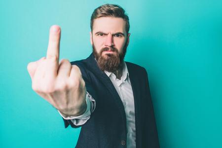 Hombre brutal está mostrando el dedo medio a la cámara. Está muy serio y enojado. Está expresando sus sentimientos. Aislado sobre fondo azul Foto de archivo