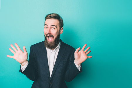 Funny man is standing and waving with his hands. He is very excited. Isolated on blue background Stok Fotoğraf - 119517162