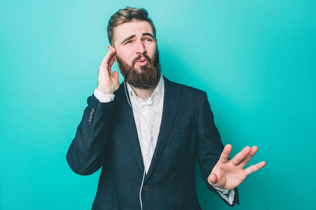 Guy in suite is staanding and listening to the music on the phone. He is enjoying the moment and looking to the right. He is holding right hand close to the ear. Isolated on blue background Stock Photo