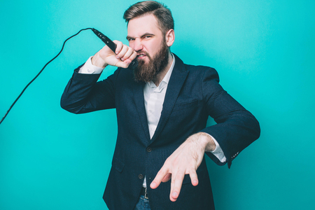 Another picture of man in suite is singing. He likes to sing in microphone. Man is loking to the camera with a serious sight. Isolated on blue background