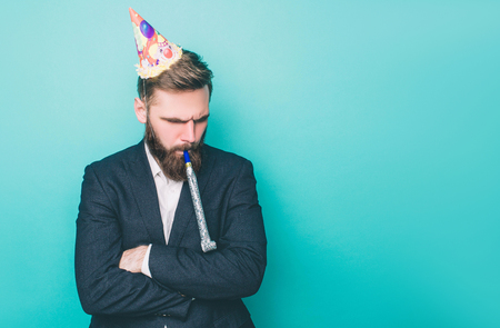 Sad guy is standing and looking down. He is upset. Man is holding a wistle in his mouth and has a birthday hat on the head. Isolated on blue background