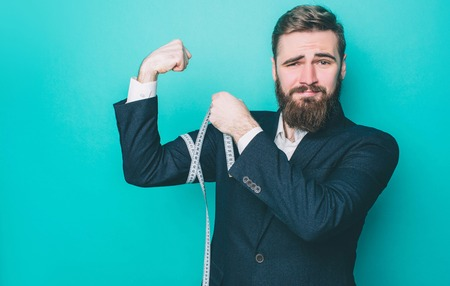 Strong and well-built bearded man is measuring his biceps with a measuring ribbon. He is happy and looks very proud. Isolated on blue background
