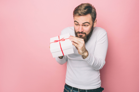 Man is holding a present in his hands. He likes it very much. Isolated on pink background