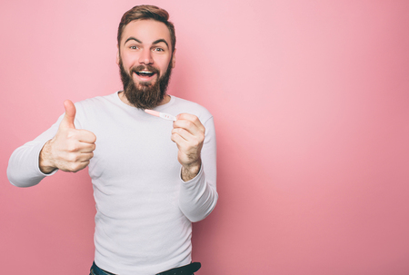 Happy guy is showing his big thumb up. He has a pregnancy test in his hands. Man is very happy. Isolated on pink background Stok Fotoğraf - 119517451