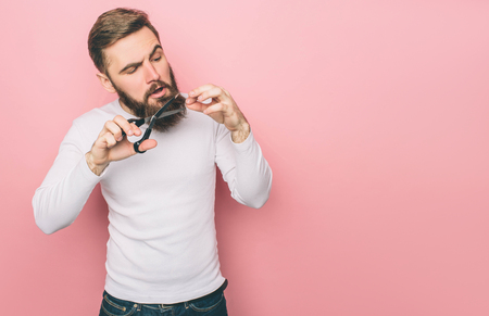 A picture of guy that cuts his beard with the scissors. He is doing that very accurate. Isolated on pink background Stok Fotoğraf