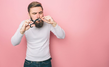 A picture of guy cutting his moustache with the scissors. He is doing that very accurate. Isolated on pink background Stok Fotoğraf