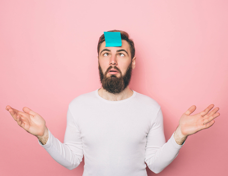 Weird guy has a blue sticker on his forehead. He is looking at it. Isolated on pink background Imagens - 119517827