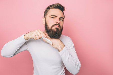 Bearded man is brushing his beard. He is doing that very tender and accurate. Isolated on pink background Stok Fotoğraf