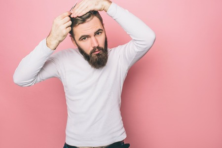Serious guy is brushing his hair. He is doing that very tender and accurate. Also man is looking down. Isolated on pink background