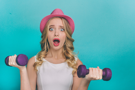 Terrified girl is holding dumbbels and looking straight on camera. The dumbbels are heavy. Its hard for girl to lift them up. Isolated on blue background.