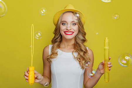 Cheerful and happy young lady is standing and looking straight forward. She is holding a thing to inflate soap balls in both her hands. She is happy very much. Isolated on yellow background.