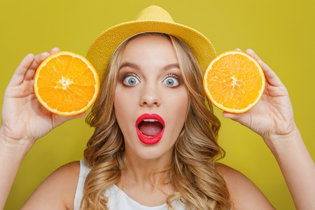 Amazed and excited young woman wears yellow hat. Also she is showing two pieces of juicy orange to camera. She is keeping her mouth wide open. Isolated on yellow background.