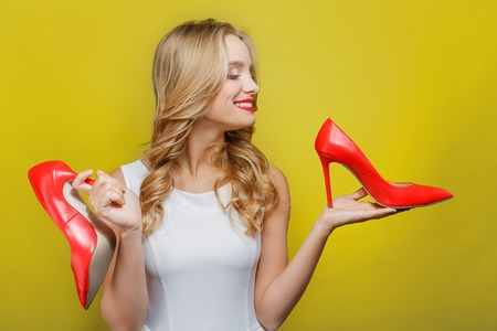 Awesome and nice girl is holding red shoes with high heels in her hands. She is looking at one of the shoe and smiling. She likes fashionable clothes. Isolated on yellow background.