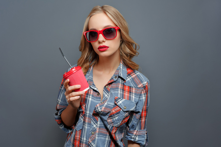 Girl with blonde hair wears dark glasses with red edge. She is holding a cup of coke. Girl is looking straight forward. Isolated on grey background. Standard-Bild - 100683897