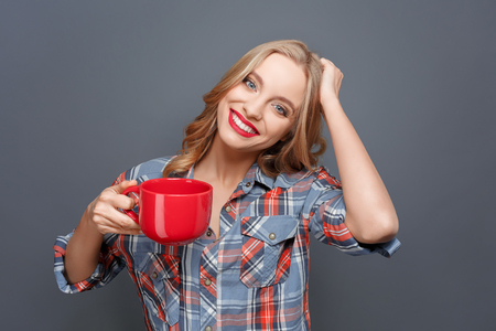 Young and pretty woman is holding a red cup in her right hand and holding her other hand on the hair. She looks happy. Isolated on grey background. Standard-Bild - 100683926