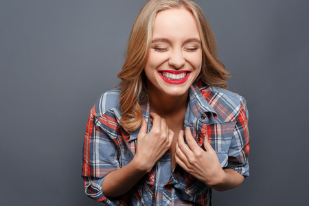 Nice and pretty young woman is laughing. She has closed her eyes. Girl is keeping her hands close to the chest. Isolated on grey background. Standard-Bild - 100683929