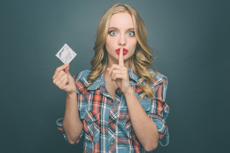 Girl is holding a condom in her hand and showing the silence symbol. She looks very serious. Isolated on blue background.