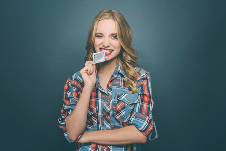 Funny firl is biting a piece of condoms package. She is looking straight forward. Isolated on blue background.