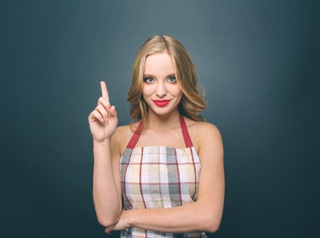 Sexy blonde girl is standing and pointing up. She looks fantastic. Also girl wears apron. Isolated on blue background. Standard-Bild - 100684166