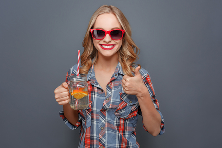 Another picture of happy person that holds a cup with juice and a piece of orange. She is showing her big thumb up. Also girl wears dark glasses with red edge. Isolated on grey background.