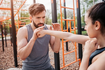 Man and woman are standing outside in the park and exercising. Girl is boxing while her trainer is helping her. Both of them look serious and conentrated.