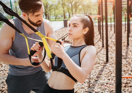 Well-built girl is doing push-ups using the loops for that. She is exercising very intense. Young man is controlling the moves that girl is doing. Stock Photo