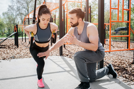 Two beautiful people are exercising. Girl is holding loops with her hands and squatting at the same time while her boyfriend is controlling her.