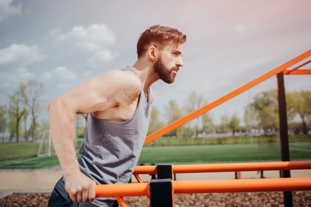 Muscular and attractive man is doing exercise on the horizontal bar ouside. He is doing push-ups. Man has an intensive workout. Stock Photo