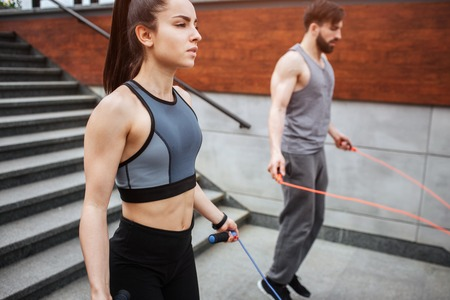 Two strong people are jumping using a rope for that. Guy is jumping more intensive that girl does. He is looking down while she is looking straight forward. Reklamní fotografie