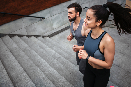Young man and woman are jogging. They are going up by steps. The couple is looking straight. They are concentrated on moving forward.