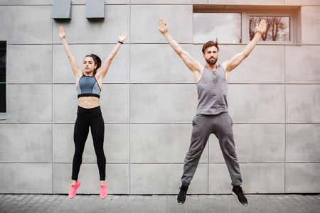 Handsome man and beautiful girl is jumping near cocnrete wall. They are keeping their hands over the head. This people are exercising.