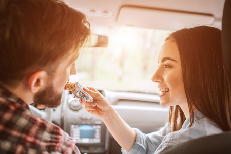 Girl is holding a sweet bar and feeding it to her boyfriend. Guy is biting a piece of bar. She is looking at him and smiling. They made a stop to eat food.