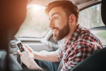 A picture of guy sitting on seat in car and holding small and white phone. He is poiting on dark screen and looking to the left. He is worried a bit.